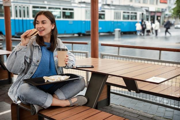 Aantrekkelijk meisje in casual stijl eet een hamburger met koffie zittend op het zomerterras van een café