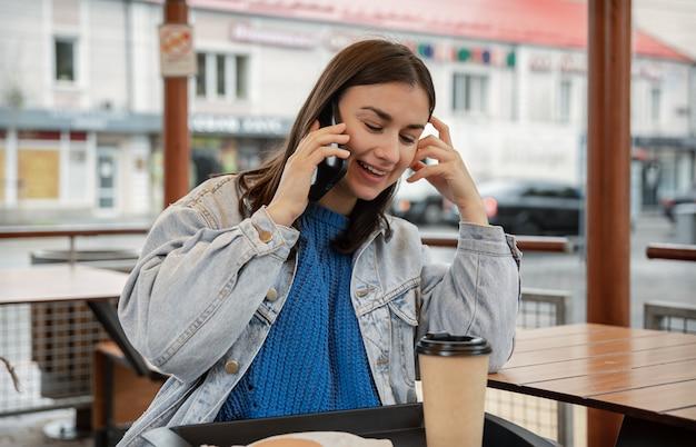 Aantrekkelijk meisje in casual stijl spreekt aan de telefoon, zittend op het terras van een café