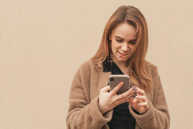 Aantrekkelijk meisje in een beige jas staat met een smartphone in de handen van een beige muur, kijkt naar het scherm van de smartphone en glimlacht