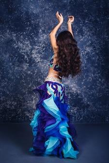 Aantrekkelijk meisje in een blauw pak buikdans dansen