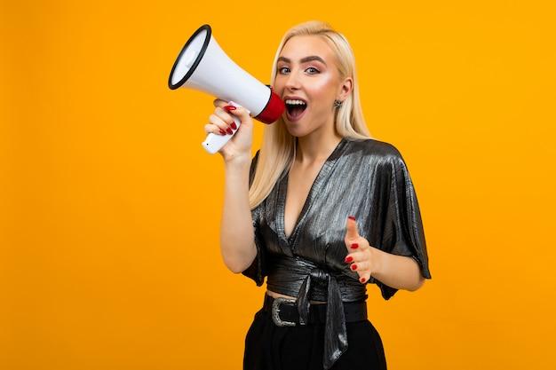 Aantrekkelijk meisje in een blouse die nieuws in een megafoon op een gele studioachtergrond schreeuwt