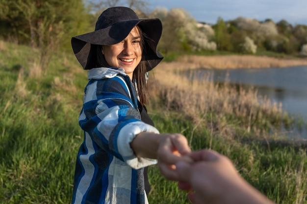 Aantrekkelijk meisje in een hoed bij zonsondergang op een wandeling langs het meer