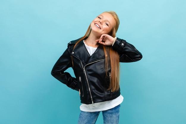 Aantrekkelijk meisje in een leren jas en spijkerbroek poseren op een lichtblauwe achtergrond met copyspace.