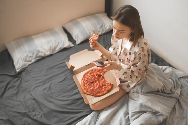 Aantrekkelijk meisje in een pyjama zit op een bed met een pizzadoos op haar schoot