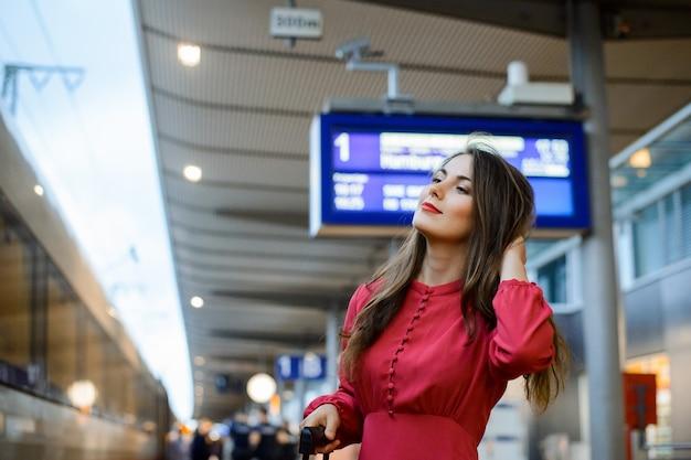 Aantrekkelijk meisje in een rode jurk met een koffer gaat op reis