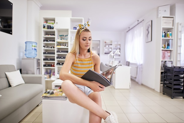 Aantrekkelijk meisje in een schoonheidssalon. ze zit op de bank en leest met belangstelling tijdschriften. de dame lacht.