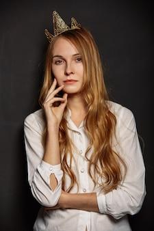 Aantrekkelijk meisje in een wit shirt met een kroon op haar hoofd