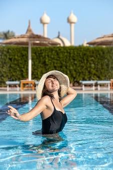 Aantrekkelijk meisje in een zwarte zwembroek en hoed baadt in het zwembad. het concept van vakantie en recreatie in een warm land.