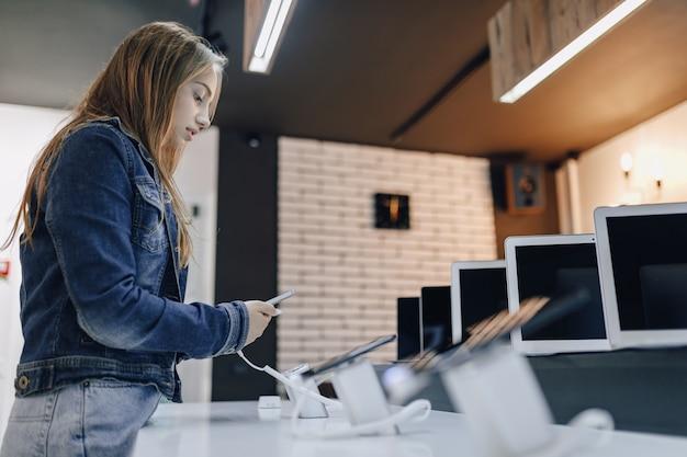 Aantrekkelijk meisje in elektronicawinkel staat aan het bureau en test telefoon