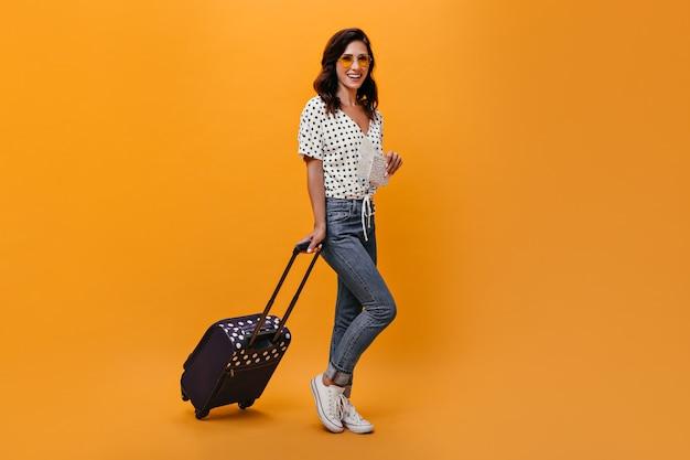 Aantrekkelijk meisje in glazen draagt koffer op oranje achtergrond. brunette met golvend haar in zonnebril in witte blouse met zwarte polka dots poseren.