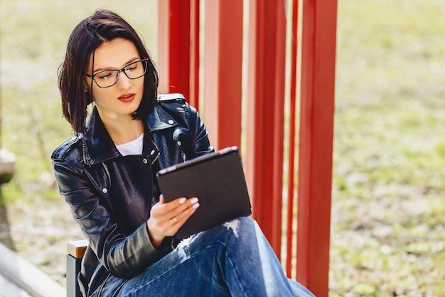 Aantrekkelijk meisje in glazen met tablet in het park