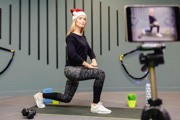 Aantrekkelijk meisje in kerstmuts doet fitness oefeningen en neemt zichzelf op voor de camera.
