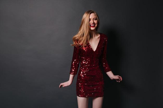 Aantrekkelijk meisje in korte jurk glimlachen naar de camera. betoverende blonde vrouw die pret heeft op feestje.