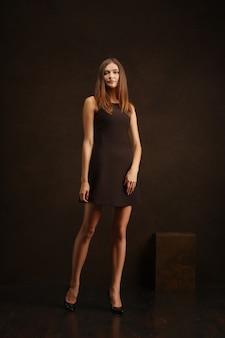 Aantrekkelijk meisje in korte jurk poseren in de buurt van donkere muur op provocerende wijze