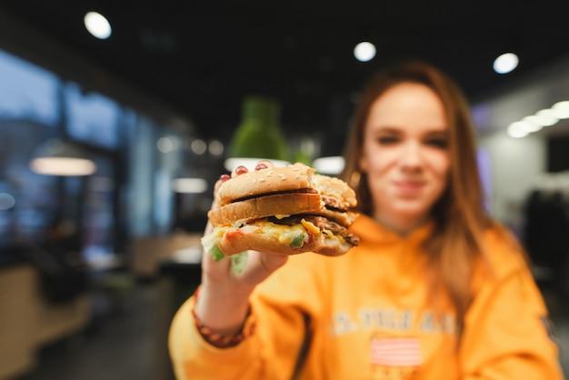 Aantrekkelijk meisje in oranje kleding met een grote smakelijke hamburger