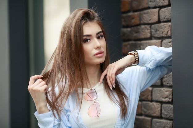 Aantrekkelijk meisje in pluizig jasje staande op straat, vangen de laatste lichten van de herfstzon. witte tanden, grote lippen, donkerbruin haar en make-up. gebouw en struiken op de achtergrond. stijlvolle dame.