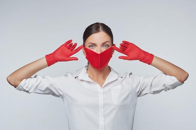 Aantrekkelijk meisje in rode handschoenen en een gezichtsmasker.