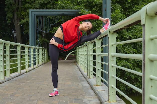 Aantrekkelijk meisje in sportkleding doet een warming-up op de brug in het stadspark.