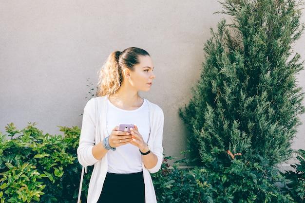 Aantrekkelijk meisje in wit vest met behulp van een mobiele telefoon buitenshuis