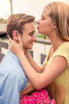Aantrekkelijk meisje kust haar vriendje voor een bloem cadeau