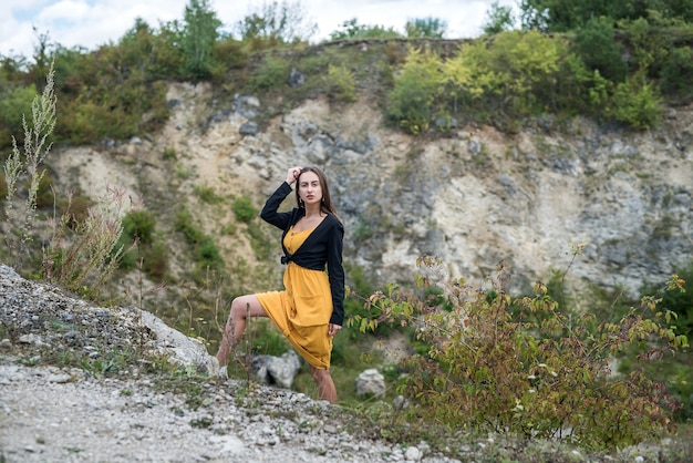 Aantrekkelijk meisje lopen en ontspannen in de zandgroeve in de buurt van stenen rots. levensstijl