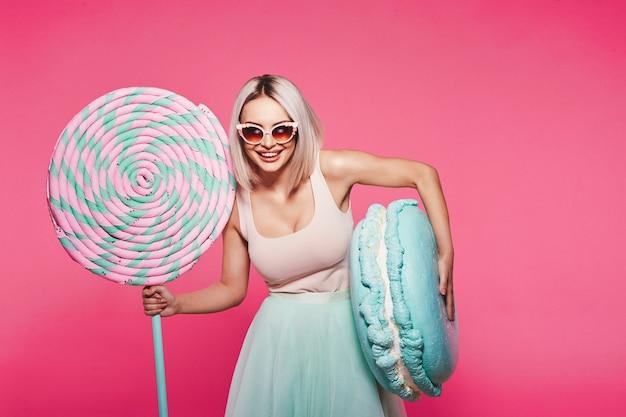 Aantrekkelijk meisje met blond haar dat een top en een rok draagt die zich met enorme zoete lollypop bevindt