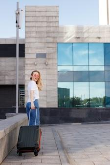 Aantrekkelijk meisje met bril met bagage gaat in de zomer op pad