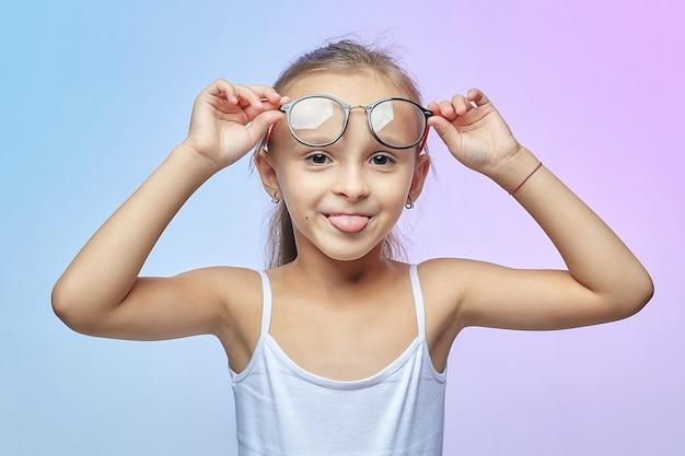 Aantrekkelijk meisje met bril toont haar tong.