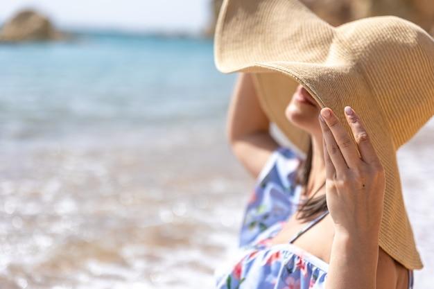 Aantrekkelijk meisje met een hoed verbergt haar gezicht voor de zon, zittend aan de kust.