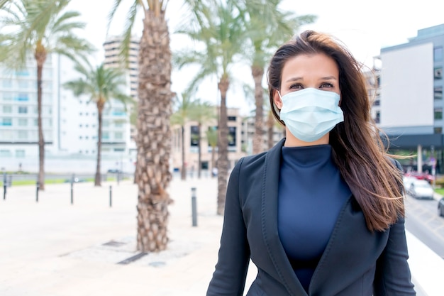 Aantrekkelijk meisje met een uitvoerende uitstraling liep werkloos met een beschermend chirurgisch masker naar voren gekeken