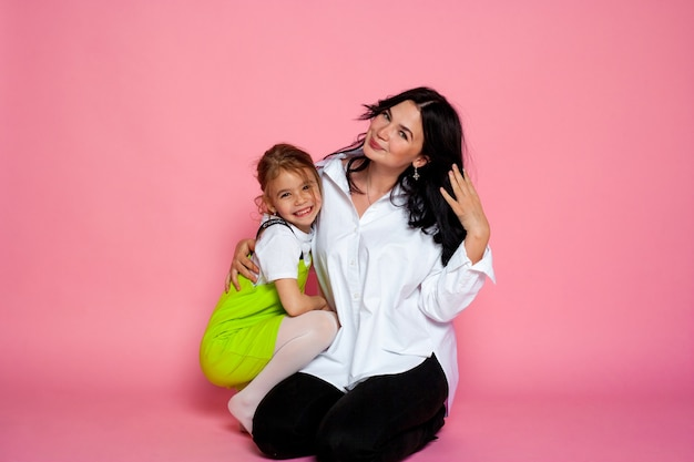 Aantrekkelijk meisje met haar moeder op de roze achtergrond