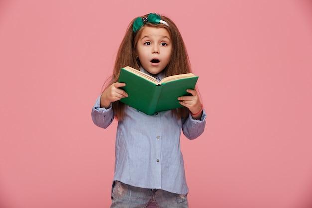 Aantrekkelijk meisje met het europese boek van de verschijningsholding in handen die rente en nieuwsgierigheid uitdrukken