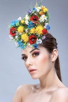 Aantrekkelijk meisje met kleurrijke lentebloemen en blote schouders, kijkend naar de zijkant.