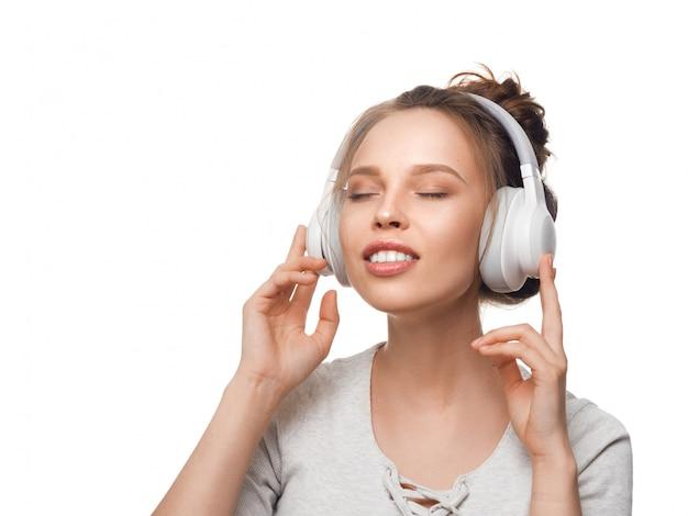 Aantrekkelijk meisje met koptelefoon op witte muur