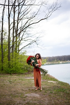 Aantrekkelijk meisje met krullend haar en een glimlach op haar gezicht met een enorm boeket rode rozen op een achtergrond van blauw meer. warme zomerdag, gelukkige jonge vrouw, emoties van vreugde