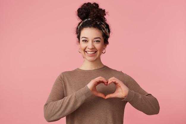 Aantrekkelijk meisje met krullend haar, stuurt een hartgebaar, glimlacht breed en kijkt naar de camera geïsoleerd op roze achtergrond.