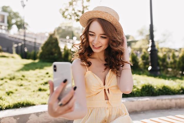 Aantrekkelijk meisje met krullend kapsel selfie maken in park. mooie gember jonge vrouw die foto van zichzelf tijdens het rusten buiten.
