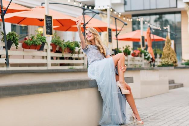 Aantrekkelijk meisje met lang blond haar in blauwe lange tule rok met plezier op terras achtergrond. ze houdt haar hand op haar been en lacht naar de camera.