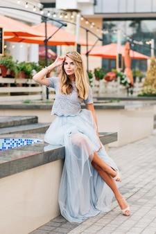 Aantrekkelijk meisje met lang blond haar in blauwe lange tule rok zittend op terras achtergrond. ze houdt haar hand op haar hoofd en kijkt naar de camera.