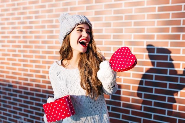 Aantrekkelijk meisje met lang haar in gebreide muts en handschoenen op muur buiten. ze houdt een open dooshart in handen en drukt naar de zijkant.