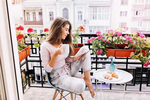 Aantrekkelijk meisje met lang haar in pyjama's ontbijten op balkon in de ochtend in de stad. ze houdt een kopje vast en leest op tablet.