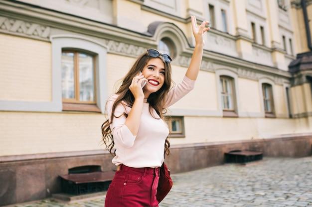 Aantrekkelijk meisje met lang kapsel loopt in de stad. ze telefoneert en stelt iemand tevreden.