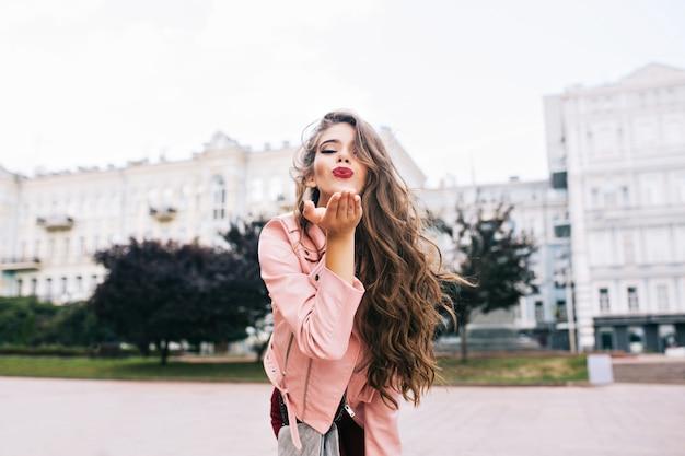 Aantrekkelijk meisje met lang kapsel met plezier in de stad. ze heeft een roze jasje en stuurt een kus met wijnlippen.