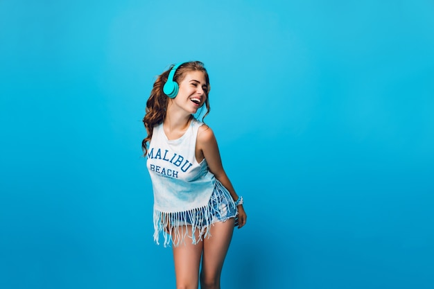 Aantrekkelijk meisje met lang krullend haar in de staart heeft plezier op blauwe achtergrond in de studio. ze draagt een wit t-shirt, een korte broek en luistert naar energieke muziek met een blauwe koptelefoon.