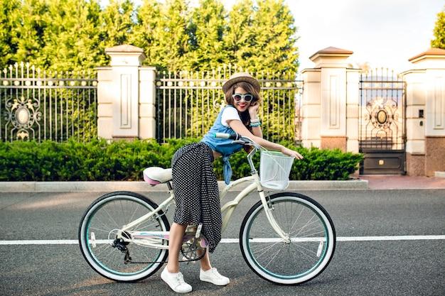 Aantrekkelijk meisje met lang krullend haar in hoed poseren met fiets op weg. ze draagt een lange rok, jerkin, blauwe zonnebril. ze lacht naar de camera.