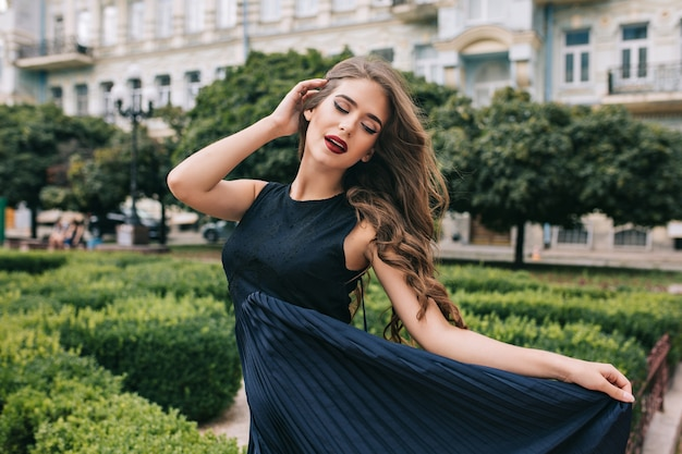 Aantrekkelijk meisje met lang krullend haar poseren in de stad