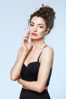 Aantrekkelijk meisje met lichte make-up poseren over blauwe muur