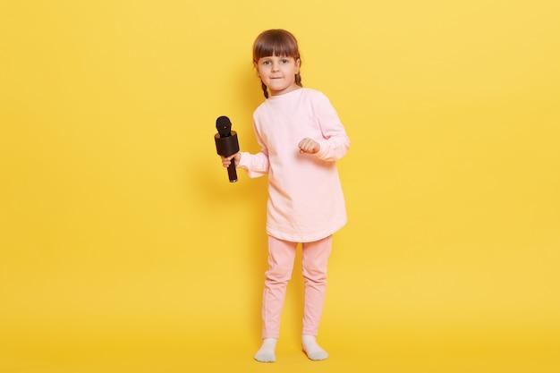 Aantrekkelijk meisje met microfoon draagt roze bleke kleding staande geïsoleerd op gele achtergrond, charmante zangeres zingt lied in karaoke, kind concert regelen.