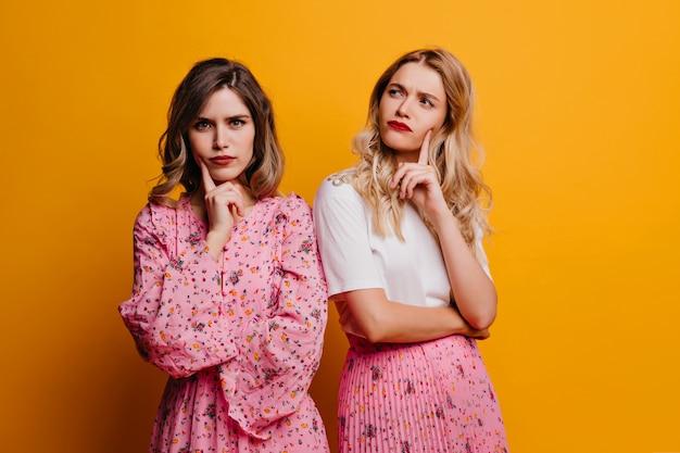 Aantrekkelijk meisje met rode lippen poseren naast vriend. europese jonge dames in roze kleren die zich op gele muur bevinden.