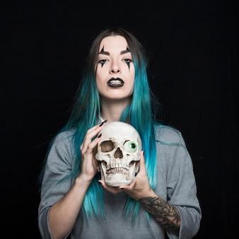Aantrekkelijk meisje met schedel met speelgoed oog